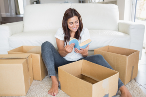 Woman looking at book from moving box in living room