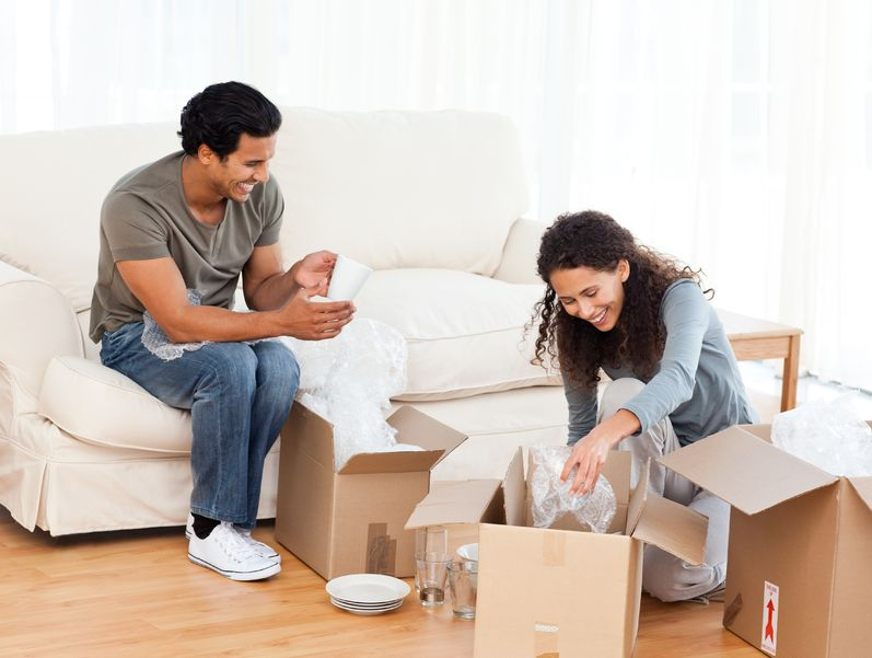 happy couple packing glasses together in the living-room